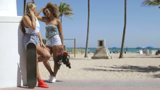 Multiracial women with rollers and skateboard standing on beach pavement in tropical sunlight and chatting happily.