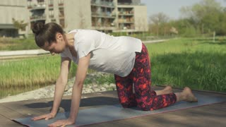 nonymous brunette in white t-shirt training child yoga pose on mat in morning