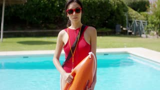 One serious beautiful young woman in red lifeguard uniform holding floatation device beside pool