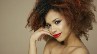 Portrait of cheerful ethnic woman with red lips touching curly hair and looking at camera in studio.