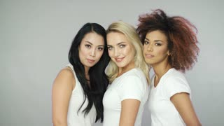 Portrait of cheerful young pretty women models in white t-shirts looking at camera and posing in studio.
