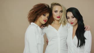 Portrait of three cheerful sensual women with red lips embracing and looking at camera while posing in studio.