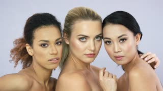 Portrait of three young attractive women with different hair looking at camera and posing in studio together.