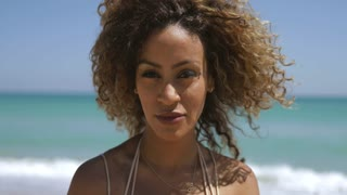 Portrait of wonderful black woman with curly hair flying in wind enjoying sunlight on tropical coastline and smiling at camera.