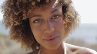 Portrait of wonderful ethnic woman with curly hair looking at camera and smiling romantically on background of beach.