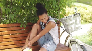Portrait of young and beautiful woman in casual summer clothing sitting and relaxing on bench looking at camera with slight smile.