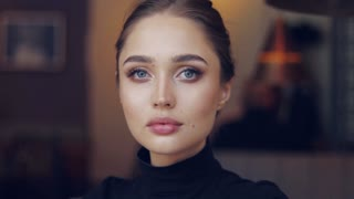 Portrait of young female in black shirt posing sensually and looking at camera on blurred background of cafe