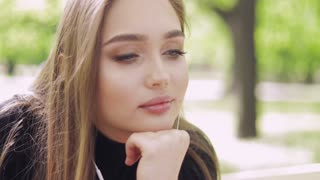 Portrait of young pretty girl sitting in headphones outside on bench with blurred green trees on background