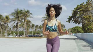 Pretty black woman in sportswear with curls in motion of running on street with tropical palms on background.