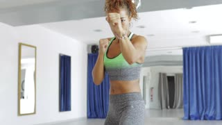 Pretty confident black woman in sportswear warming up and boxing in dance class alone.