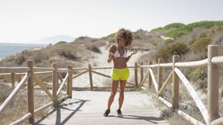 Pretty content model in swimsuit and shorts walking on pier with smartphone and enjoying music with headphones on background of ocean shoreline.