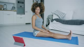 Pretty ethnic model in gray shorts sitting on mat at home watching video on tablet and practicing yoga stretching legs.