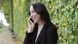 Pretty smiling woman in black jacket and polo-neck shirt speaking on phone during her walk in autumn park.