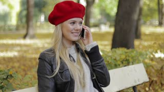 Pretty woman in leather jacket and red beret sitting on bench and speaking on phone and smiling during her walk in autumn park.