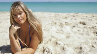 Pretty women in bikini and with long blond hair lying on sandy coast in tropical sunlight smiling alluringly at camera.