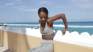 Pretty young ethnic woman leaning on fence and doing push-ups exercise while working out at seaside.