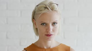 Pretty young female with short blond hair and glasses looking at camera and applying smooth cream on face while standing on white background