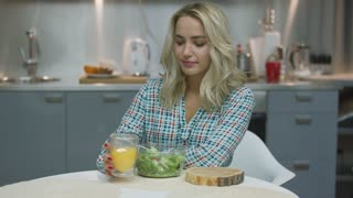 Pretty young woman drinking yummy orange juice and eating healthy salad while sitting at kitchen.