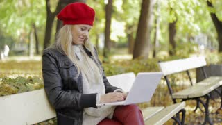 Pretty young woman in black leather jacket and red beret sitting on bench and using laptop during her walk in autumn park.
