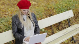 Pretty young woman in black leather jacket and red beret sitting on bench in autumn park and using laptop on sunny day.