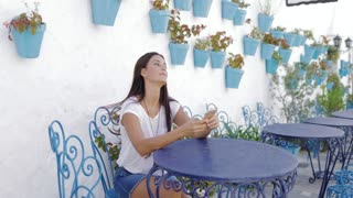 Pretty young woman in casual clothing relaxing at table in tropical resort garden and browsing smartphone.