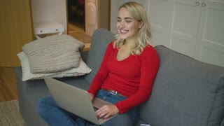 Pretty young woman in casual outfit browsing laptop and cheerfully smiling while sitting on comfortable couch.