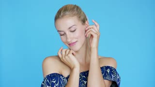 Pretty young woman in ornamental clothing touching soft skin of face and looking at camera while standing on blue background