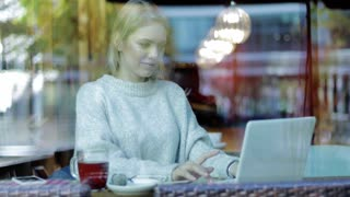 Pretty young woman in soft beige jumper sitting behind window, drinking coffee and using her laptop.