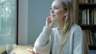Pretty young woman in soft beige jumper sitting near bookcase, listening to music and looking at window.