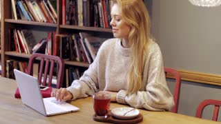 Pretty young woman in soft jumper sitting in library with mug of hot tea,using her laptop and enjoying silence.