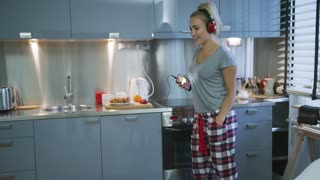 Pretty young woman in T-shirt and checkered pants standing in stylish kitchen and listening to good music.