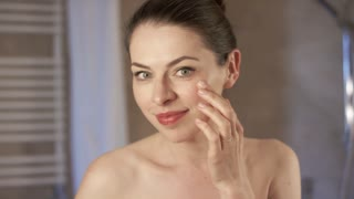 Pretty young woman looking at mirror and applying soft cream on delicate skin while standing in bathroom in morning.
