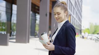 Pretty young woman wearing formal shirt and jacket standing on street with cup of coffee in hands and using smartphone with headphones.