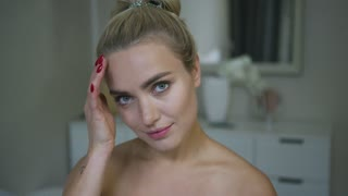 Pretty young woman with ponytail touching hair and looking at camera during everyday beauty routine in bathroom.