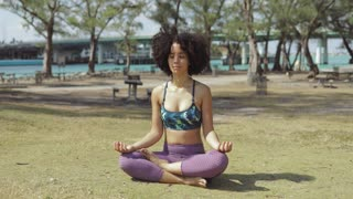 Relaxed fit black girl in sportswear sitting with legs crossed on green meadow in park and meditating with eyes closed.