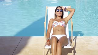 Relaxed pretty young woman wearing sunglasses and a bikini sitting sunbathing in a deck chair at the edge of a swimming pool