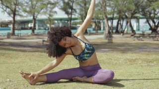 Relaxing young black woman in sportswear sitting on green meadow in park and bending on side stretching spine.
