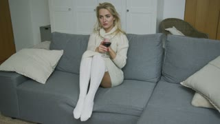 Sensual drunk woman in white dress and stockings sitting on sofa with glass of wine and hiding face.