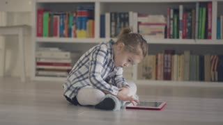 Serious little girl in shirt sitting alone on room floor and tapping tablet looking focused on game.