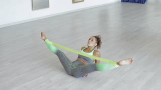 Serious young woman in sportswear lying on floor with legs tied with elastic band and stretching them during workout.