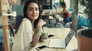 Serious young woman working at a laptop computer seated at a restaurant table enjoying a green smoothie turning to smile quietly at the camera