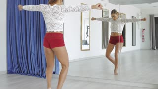 Sexual young woman in shorts standing barefoot in front of mirror in studio and performing sensual dance practicing alone.
