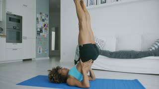 Shaped young model in sportswear lying on mat in living room and holding legs up while practicing exercise and stretching body.