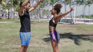 Side view of athletic ethnic young man and woman standing with hands apart and stretching while working out in the park.