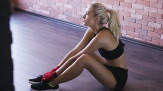 Side view of attractive young female in black sportswear sitting on lumber floor in gym and looking at camera