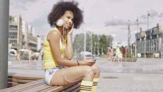 Side view of beautiful ethnic woman in summer clothing sitting on bench on urban background holding smartphone and listening to music with headphones.