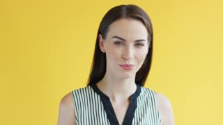 Side view of beautiful positive lady in striped clothing looking at camera while standing on bright yellow background