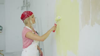 Side view of beautiful young female in white overalls and bandana using roller with pastel yellow paint on white plastered wall