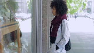 Side view of black woman with curly hair in casual clothing standing near shop window and looking ar jewelry.