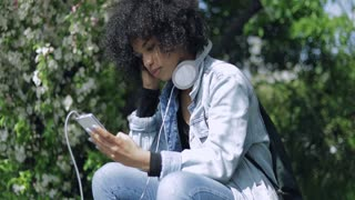 Side view of casual African girl with smartphone in hands listening to music with big headphones on background of park.